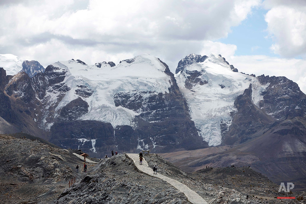 "In this Aug. 12, 2016 photo, a group of tourists walk backdropped by the Tuco"" glacier in the Huascaran National Park, in a tour called ""Route of climate change"" in Huaraz, Peru. The tropical glaciers of South America are dying from soot and rising temperatures, threatening water supplies to communities that have depended on them for centuries. (AP Photo/Martin Mejia)"
