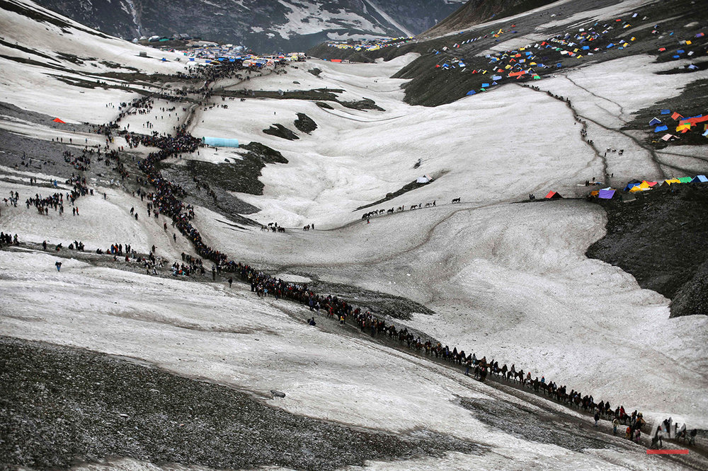 In this June 28, 2012 file photo, Indian Hindu pilgrims walk in line as they journey to the to the remote Himalayan shrine of Amarnath at 3,888 m (12,756 ft) above sea level to worship an icy stalagmite representing Shiva, the Hindu god of destruction, near Shashnag, 115 kms (71 miles) from Srinagar, India. In 2008, a government decision, later revoked, to transfer land to the Hindu shrine in Kashmir set off a summer of protests. The next year, the alleged rape and murder of two young women by government forces set off the violence. In 2010, the trigger was a police investigation into allegations that soldiers shot dead three civilians and then staged a fake gun battle to make it appear the dead were militants and claim rewards for the killings. at least 200 people were killed and hundreds wounded as troops fired live ammunition into the crowds as young men and women took to the streets, hurling rocks and abuse at Indian forces. (AP Photo/Kevin Frayer)