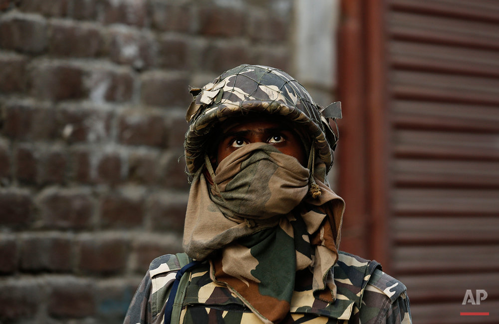 An Indian soldier stands guard during a protest in Srinagar, Indian controlled Kashmir, Friday, July 15, 2016. Clashes between Indian troops and protesters continued despite a curfew imposed in the disputed Himalayan region to suppress anti-India violence following the Friday killing of Burhan Wani, chief of operations of Hizbul Mujahideen, Kashmir's largest rebel group. (AP Photo/Mukhtar Khan)