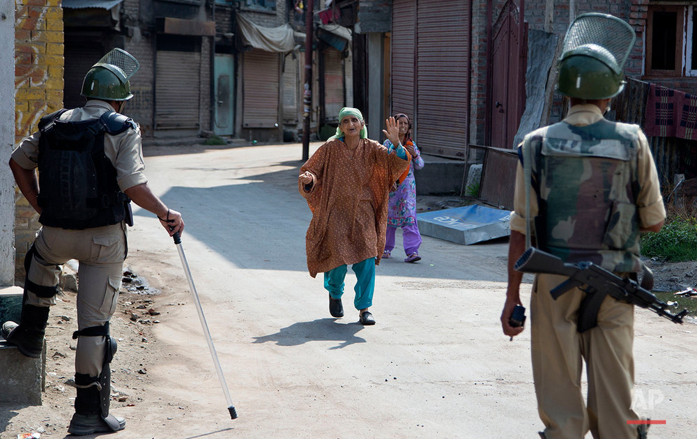 A Kashmiri woman pleads with Indian paramilitary soldiers to let her cross a temporary checkpoint during curfew in Srinagar, Indian controlled Kashmir, Tuesday, July 12, 2016. Curfew imposed in the disputed Himalayan region continues for the fourth consecutive day to suppress anti-India violence following the Friday killing of Burhan Wani, chief of operations of Hizbul Mujahideen, Kashmir's largest rebel group. (AP Photo/Dar Yasin)