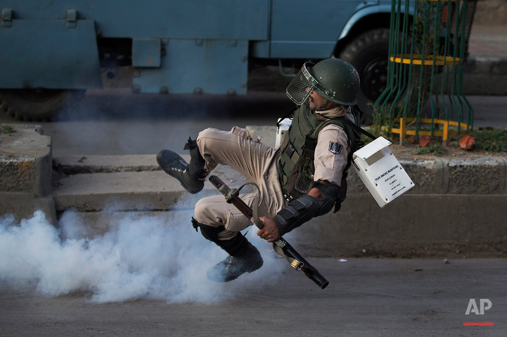 An Indian paramilitary soldier falls down as he tries to kick back an exploded tear gas shell thrown back at them by Kashmiri Muslim protesters at the end of a day long curfew in Srinagar, Indian controlled Kashmir, Monday, Aug. 8, 2016. Kashmir has been under a security lockdown and curfew since the killing of a popular rebel commander on July 8 sparked some of the largest protests against Indian rule in recent years. (AP Photo/Dar Yasin)