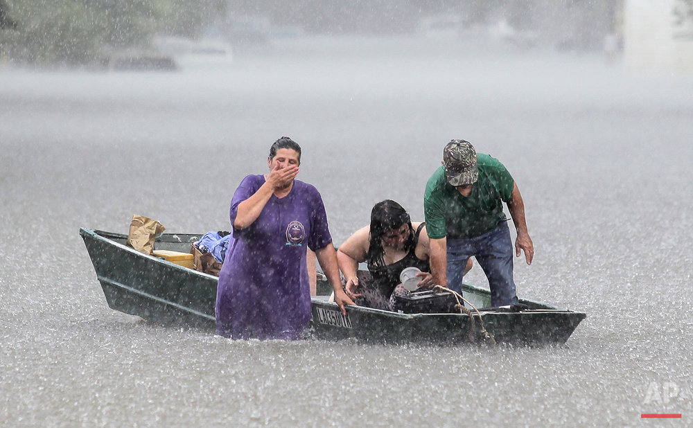 Dee Vazquez, from left, helps Georgette Centelo and her grandfather Lawrence Roberts after they tried to recover their belongings from a family mobile home in Central, north of Baton Rouge, La., Monday, Aug. 15, 2016. (David Grunfeld/NOLA.com The Times-Picayune via AP)