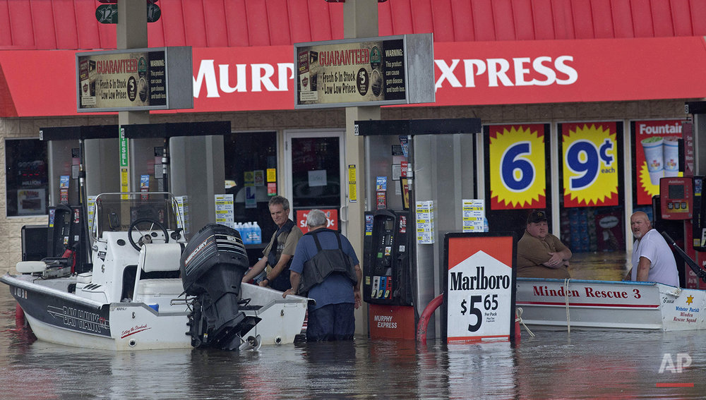Boats refuel at a gas station as they rescue people from rising floodwater near Walker, La., after heavy rains inundated the region, Sunday, Aug. 14, 2016. (AP Photo/Max Becherer)