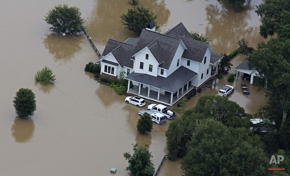 In this aerial photo over Amite, La., flooded homes are seen from heavy rains inundating the region, Saturday, Aug. 13, 2016. (AP Photo/Max Becherer)