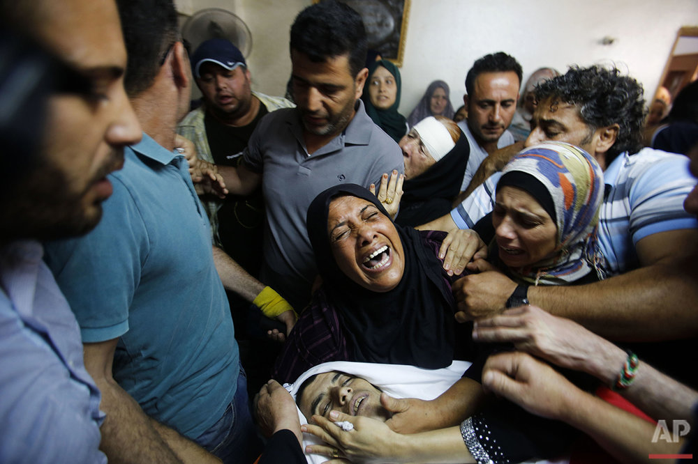 Relatives mourn over the body of Palestinian Mohammed Abu Hashhashi, 17, during his funeral in the West Bank refugee camp Fawwar, near Hebron, Wednesday, Aug. 17, 2016. Abu Hashhashi was killed by live fire during clashes between Israeli troops and Palestinians the day before. (AP Photo/Nasser Shiyoukhi)