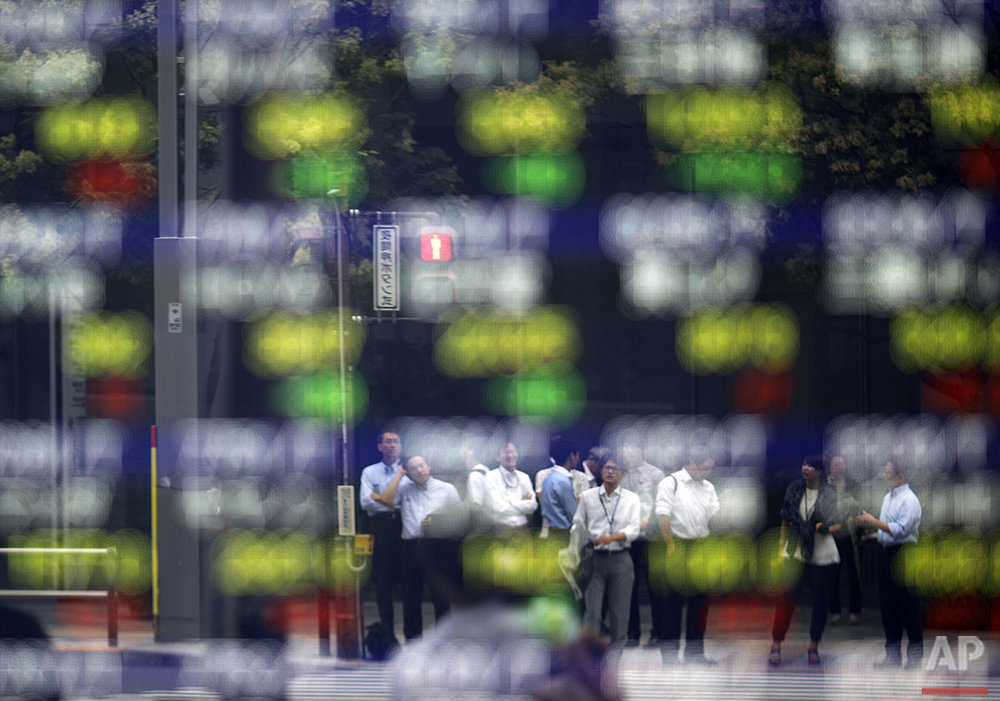 Pedestrians are reflected in an electronic board showing stock prices in Tokyo, Tuesday, Aug. 16, 2016. (AP Photo/Shuji Kajiyama)