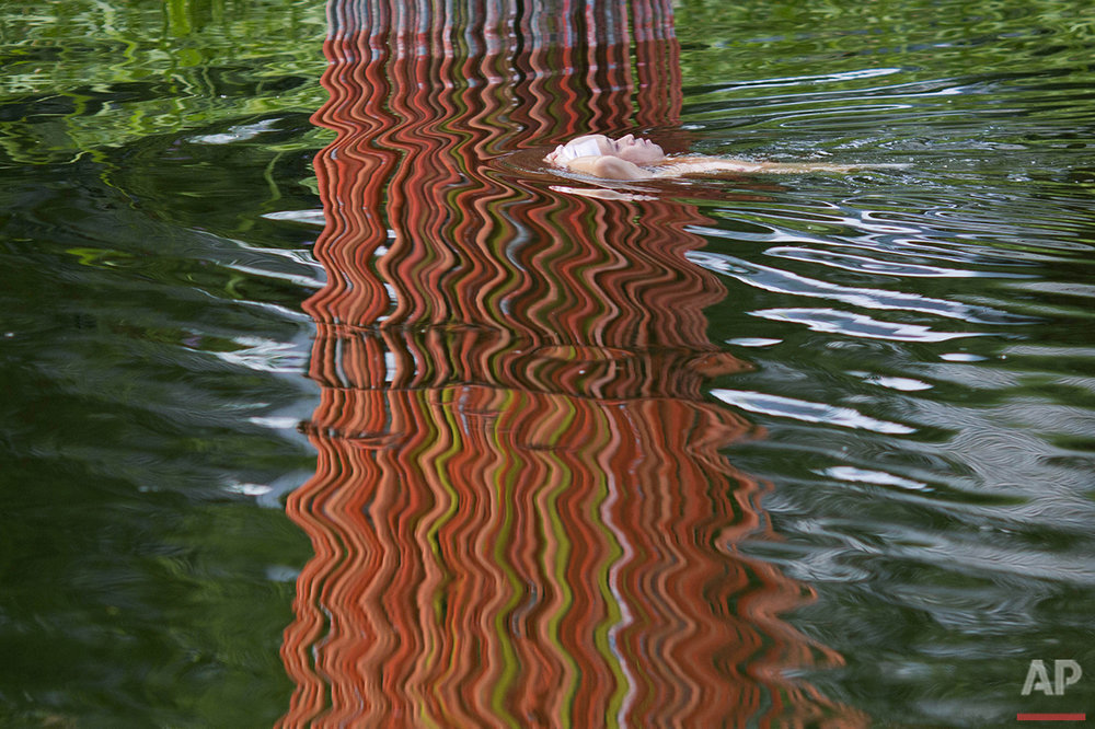A man floats past the reflection of a public sculpture next to a river in Beijing, Monday, Aug. 15, 2016. Swimming in the capital's rivers is a popular pastime in summer and even in the frigid winter. (AP Photo/Ng Han Guan)