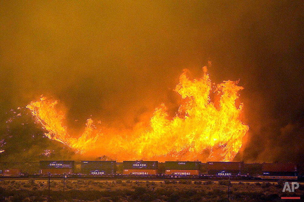 Flames burn on a hillside alongside one of the main rail routes connecting Southern California with points north and east in Cajon Pass north of Devore, Calif., Tuesday, Aug. 16, 2016. (Doug Saunders/The Sun via AP)