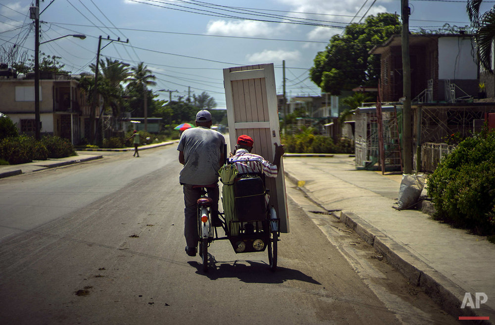 In this June 11, 2016 photo, a man carries a house door on the passenger side of a bicycle taxi in Holguin, Cuba, the region where Fidel Castro and his brother President Raul Castro were born and grew up. Fidel Castro has written of happy memories of his countryside childhood, but he has shown little attachment to the place itself. (AP Photo/Ramon Espinosa)