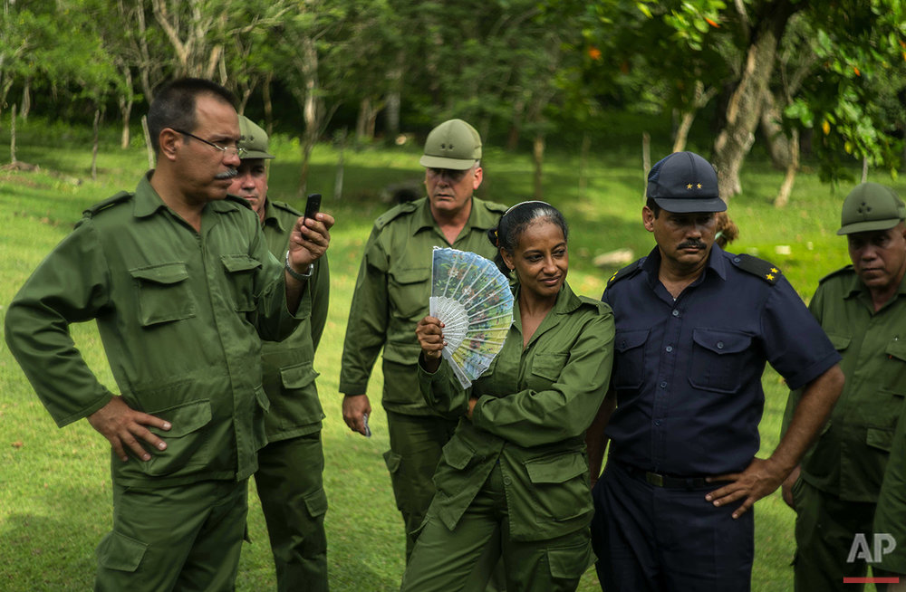 In this June 10, 2016 photo, a soldier uses a fan to keep cool as she takes a guided tour, with her colleagues from the Revolutionary Armed Forces, of the home-turned-museum where Fidel Castro and his brother, President Raul Castro, grew up in Biran, Cuba. The Castro farm was the first to be expropriated under Cuba's move toward collectivized agriculture. (AP Photo/Ramon Espinosa)