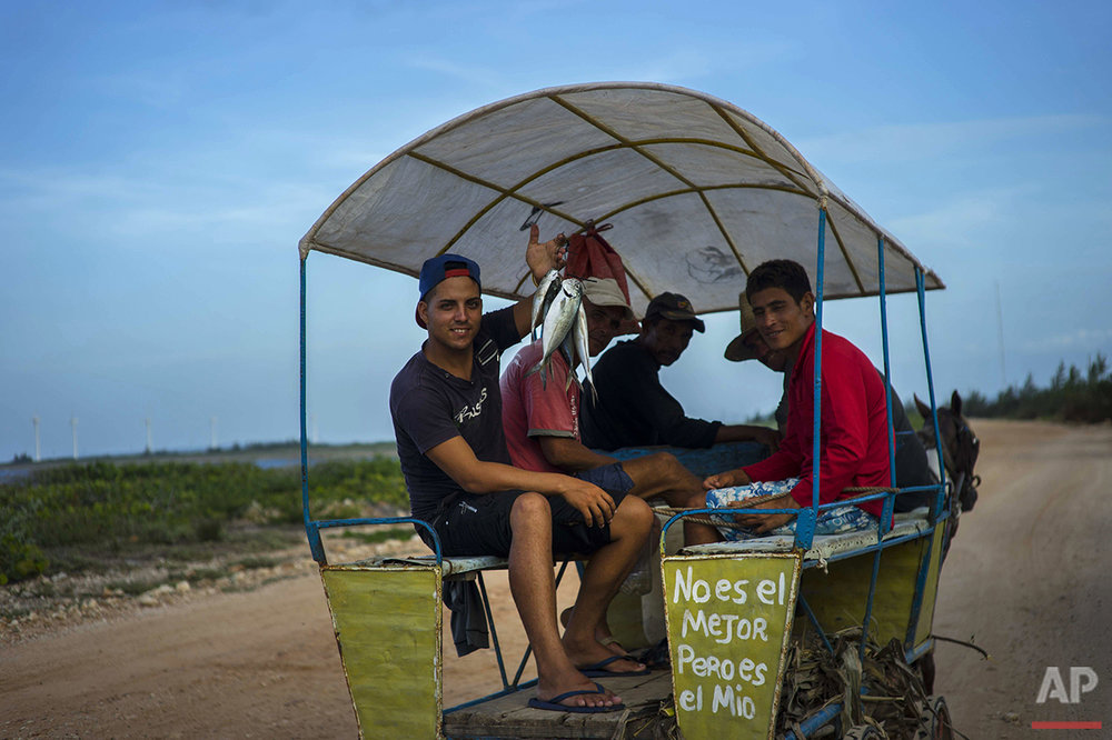 "In this June 11, 2016 photo, a message that reads in Spanish ""It's not the best but it's mine"" adorns a horse-drawn wagon with men selling sea-caught fish as they ride along the coastline near Gibara in Cuba's Holguin province. Amid the rise in visitors to the region where Fidel Castro was born, which includes the provincial capital of Holguin, locals farm, raise livestock and travel the area's dirt roads by bicycle and horse cart. (AP Photo/Ramon Espinosa)"
