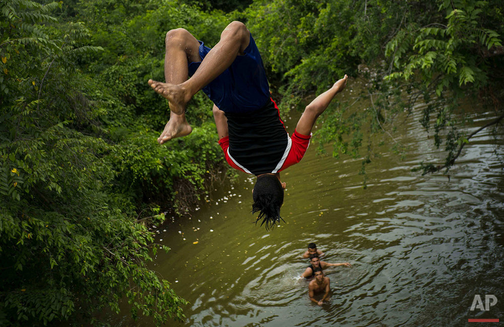 In this June 12, 2016 photo, a youth does a back flip from an overpass into the Mayari River as he and friends spend their Sunday afternoon in the village of Mayari, in Cuba's Holguin province where Fidel Castro grew up. Alcides Leyva, who directs the Castro homestead, said the former leader had signed plans to flood the property under a reservoir in the 1960s until his secretary, Celia Sanchez, intervened to save it. (AP Photo/Ramon Espinosa)