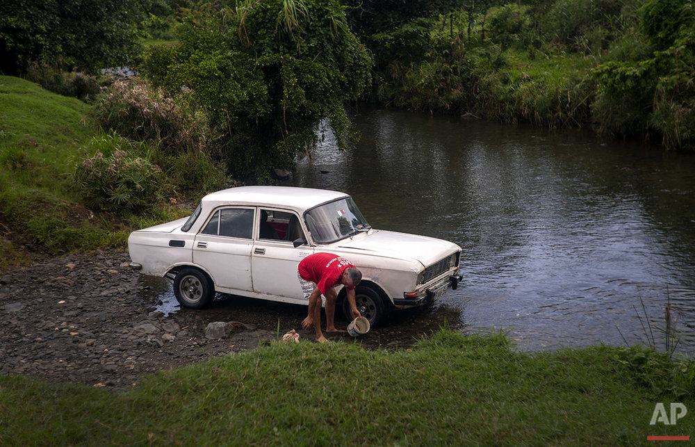 In this June 10, 2016 photo, government contracted driver Ricardo Reidy washes a Soviet-made car in the Biran River near the home-turned-museum where Fidel Castro and his brother, President Raul Castro, were born in Biran, Cuba. (AP Photo/Ramon Espinosa)