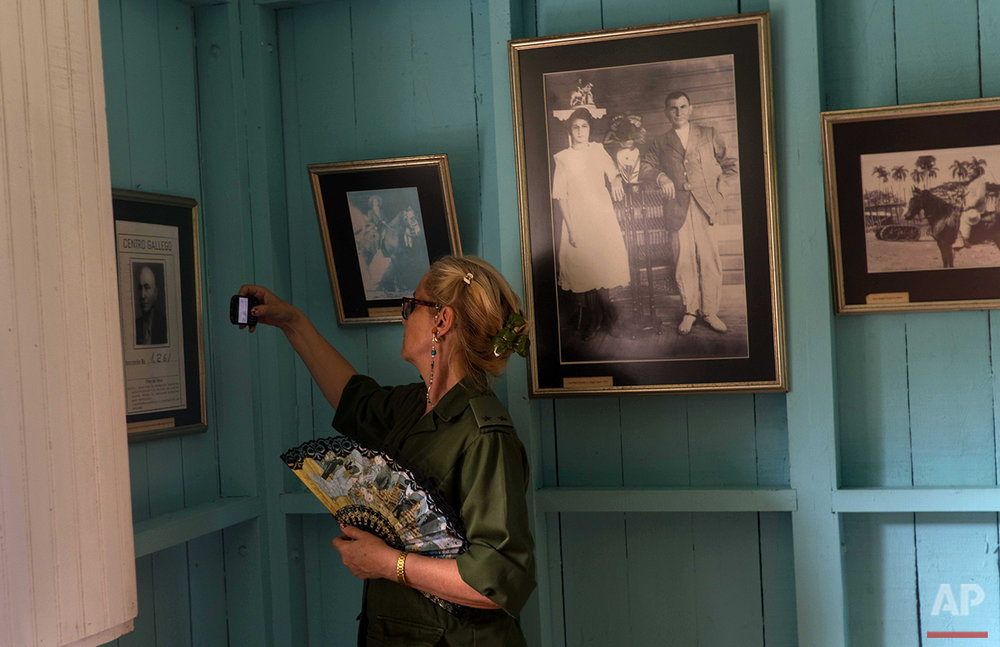 In this June 10, 2016 photo, a soldier takes photos at the home-turned-museum of Fidel Castro and his brother, President Raul Castro, where they grew up in Biran, Cuba. A large portrait of Fidel's parents, Angel Castro and Lina Ruz hangs behind her. (AP Photo/Ramon Espinosa)