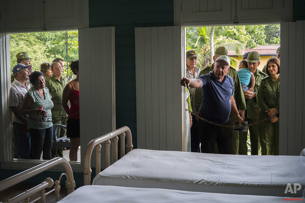 In this June 10, 2016 photo, a guide shows tourists and visiting soldiers the bedroom that was shared by Fidel Castro and his brothers at the home-turned-museum where the Castro brothers grew up in Biran, Cuba. Museum director Lazaro Castro, no relation to Fidel, said 27,800 people visited the often-sweltering site in 2015, two-thirds Cubans, and 31,000 so far this year, with the same mix of foreigners and Cubans. (AP Photo/Ramon Espinosa)
