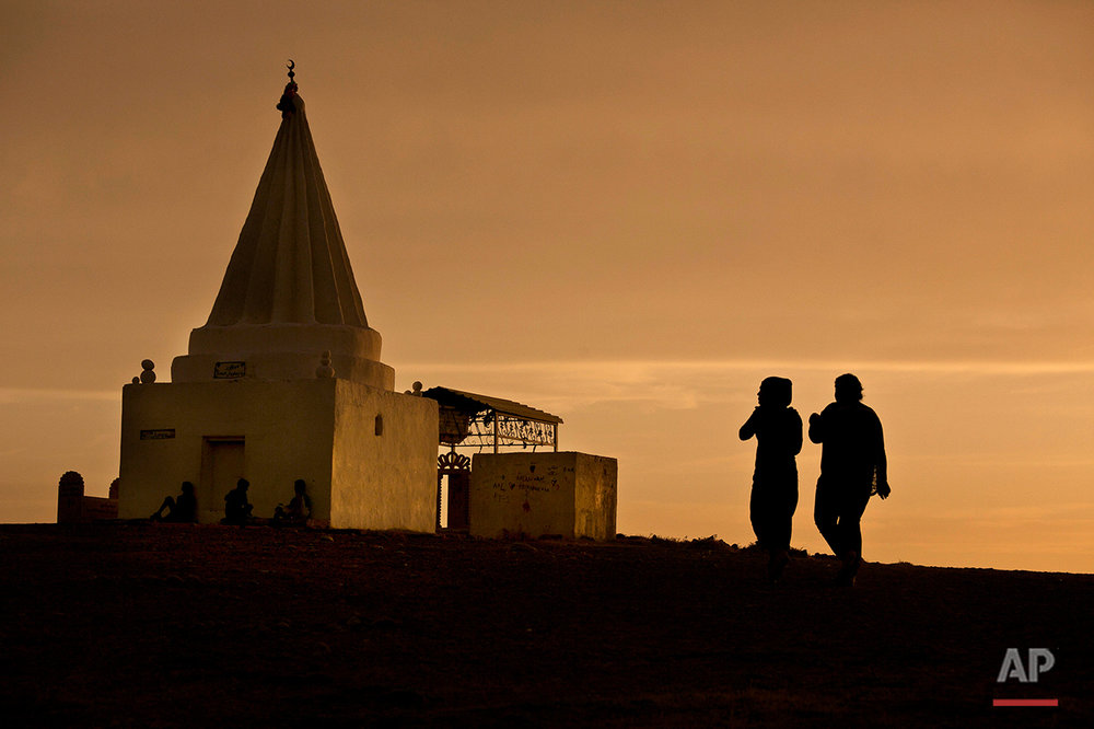 The sun sets as women visit a Yazidi shrine overlooking at Kankhe Camp for the internally displaced in Dahuk, northern Iraq, in this Wednesday, May 18, 2016 photo. The Islamic State group enslaved thousands of women from the persecuted minority Yazidi religious community when it overran their homeland in northern Iraq in 2014. Odds of rescue for an estimated 3,000 still in the extremists' hands are growing slimmer. IS has targeted smugglers who freed many slaves, money is running out to buy more girls' freedom, and the militants are tightening their grip on their captives to prevent runaways. (AP Photo/Maya Alleruzzo)