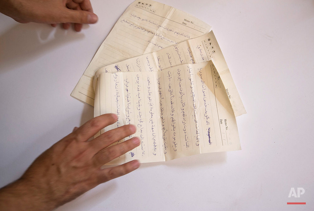 An activist documenting Islamic State group crimes against Yazidis arranges the pages of a diary written by a Yazidi girl while in Islamic State militant captivity, in this May 22, 2016, photo taken in Dahuk, northern Iraq. Some 2,500 Yazidi women and girls have escaped IS slavery through paid smugglers, but the numbers of those reaching freedom is dropping as militants tighten their grip on their sex slaves. About 3,000 are believed to be still be in IS hands. (AP Photo/Maya Alleruzzo)