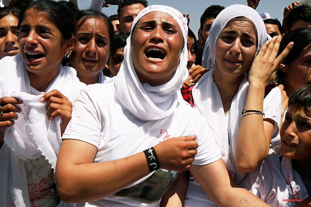 Yazidi Kurdish women chant slogans during a protest against the Islamic State group's invasion on Sinjar city one year ago, in Dohuk, northern Iraq, Monday, Aug. 3, 2015 . Thousands of Yazidi Kurdish women and girls have been sold into sexual slavery and forced to marry Islamic State militants, according to Human Rights organizations, Yazidi activists and observers. (AP Photo/Seivan M.Salim)