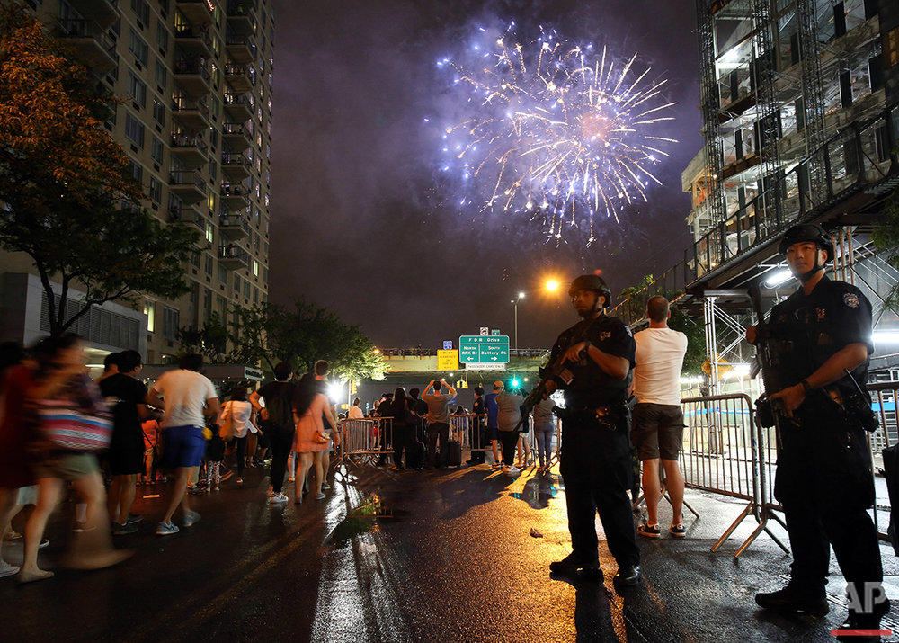 Counterterrorism police officers watch over spectators for the Fourth of July fireworks along the East River in New York on Monday, July 4, 2016. (AP Photo/Adam Hunger)