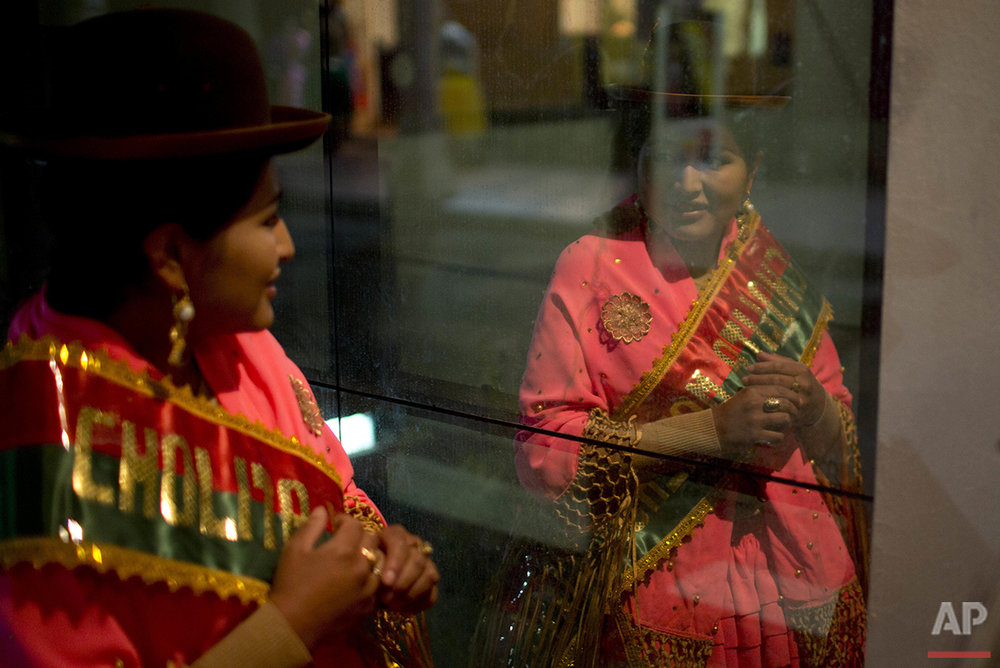 An Aymara woman looks at her reflection as she prepares to compete in the Miss Cholita 2016 pageant in La Paz, Bolivia, Friday, July 1, 2016. Cholita is the style of clothing worn by many of the country's indigenous women. (AP Photo/Juan Karita)