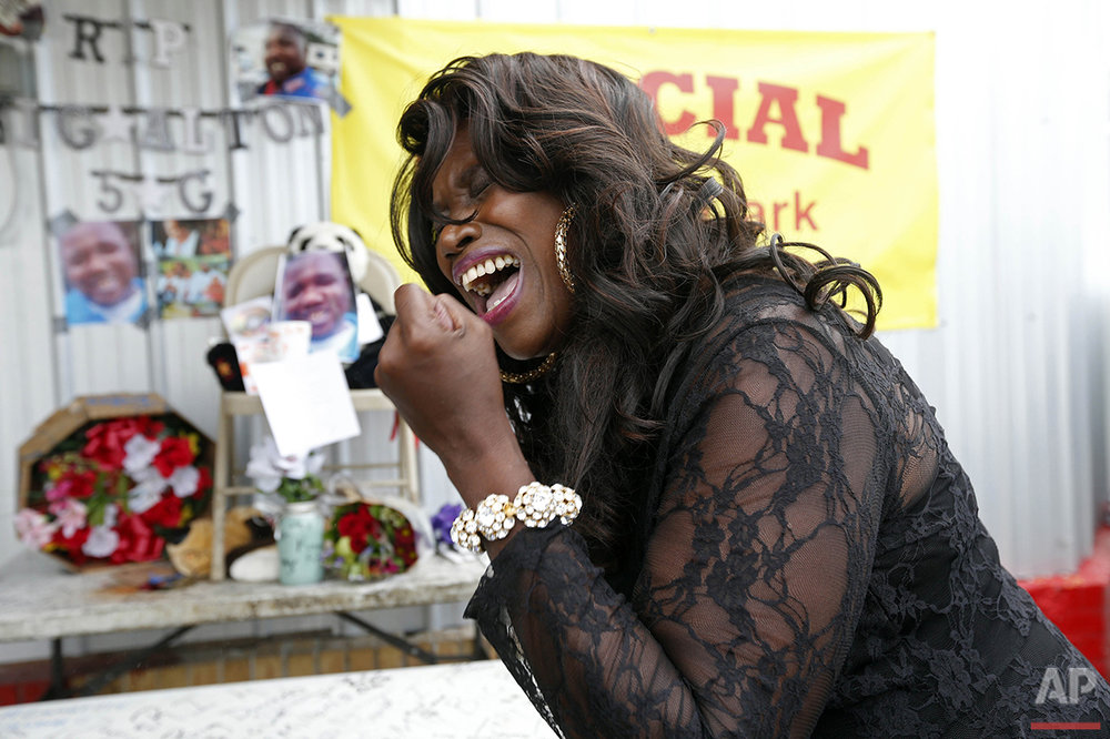 Stephanie McDee sings a song and protests at a makeshift memorial for Alton Sterling in Baton Rouge, La., Wednesday, July 6, 2016. Sterling was shot and killed by Baton Rouge police outside the convenience store where he was selling CDs. (AP Photo/Gerald Herbert)