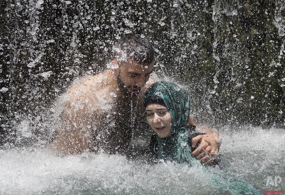 Israeli Arabs stand under a waterfall during the Eid al-Fitr holiday at the Gan HaShlosha national park near the northern Israeli town of Beit Shean, Friday, July 8, 2016. Eid al-Fitr marks the end of the Muslim holy fasting month of Ramadan. (AP Photo/Oded Balilty)