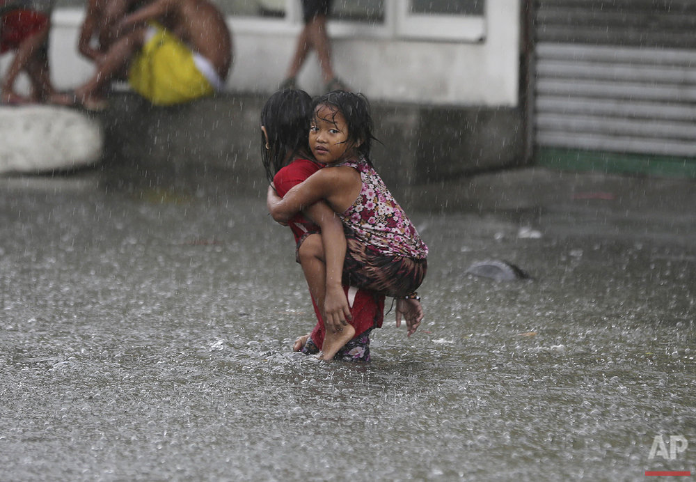 A girl is carried along a flooded road in suburban Mandaluyong, east of Manila, Philippines, as monsoon downpours intensify while Typhoon Nepartak leaves the country on Friday, July 8, 2016. (AP Photo/Aaron Favila)