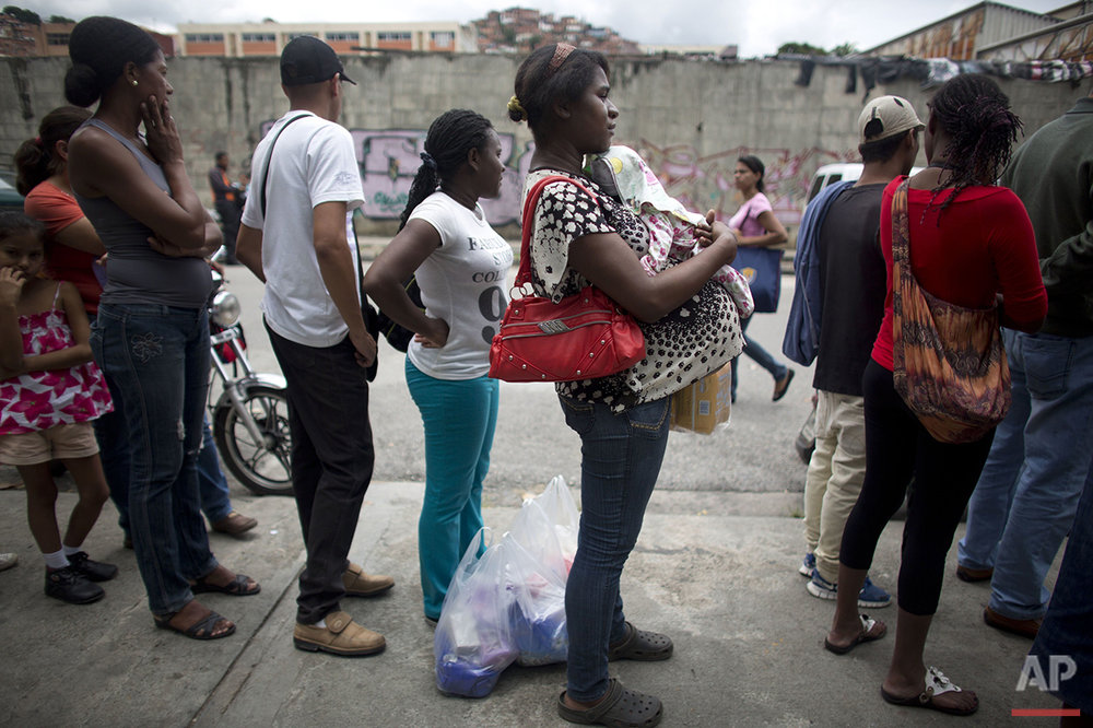 In this Monday, May 2, 2016 photo, a pregnant woman waits in line outside a supermarket to buy food in Caracas, Venezuela. At some stores, pregnant women and the elderly get their own priority lines, but not at this store. (AP Photo/Ariana Cubillos)