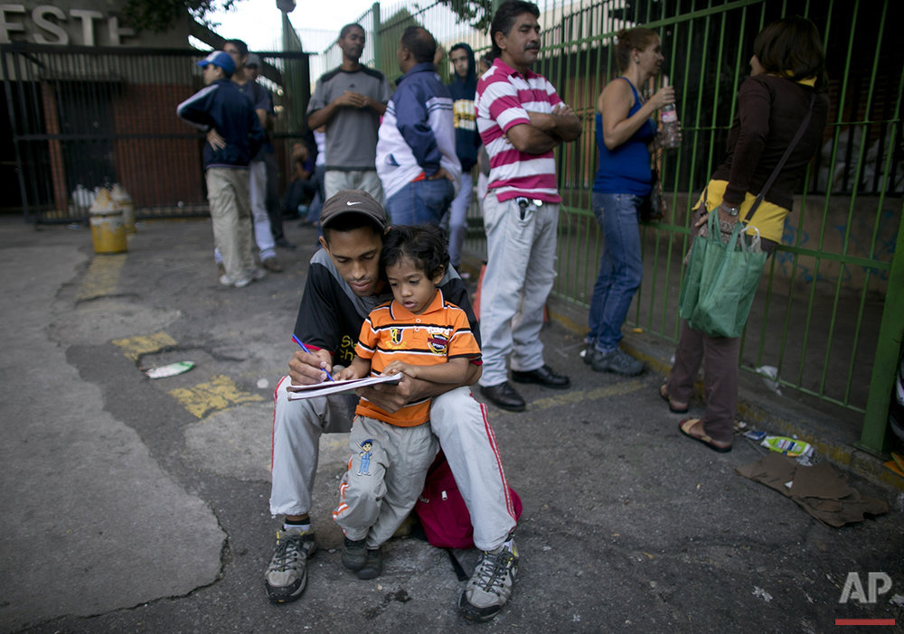 In this Monday, July 4, 2016 photo, Eder Noriega, 25, teaches numbers to his 3-year-old son Santiago as they wait in line to buy food outside a supermarket in Caracas, Venezuela. As lines in this South American country grow longer they have become a stage for everyday life. (AP Photo/Ariana Cubillos)
