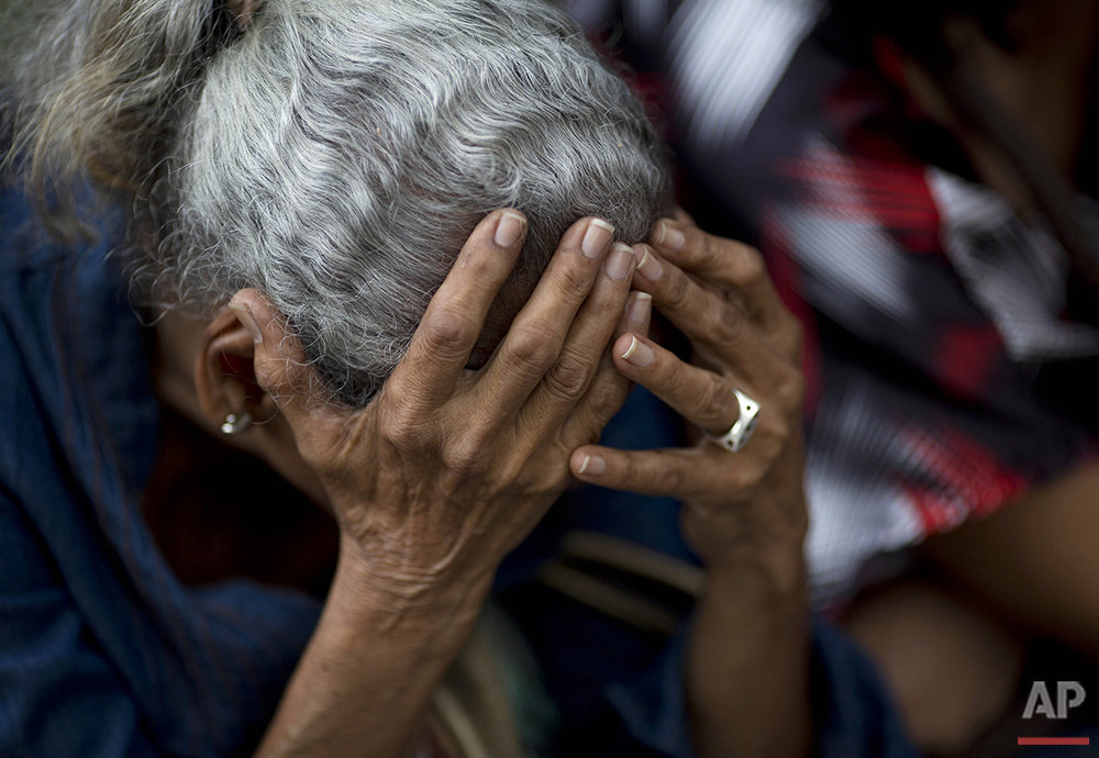 In this Tuesday, May 3, 2016 photo, a woman holds her head as she waits in line outside a supermarket to buy food in Caracas, Venezuela. Nine out of 10 people here say they can't buy enough to eat, according to a study by Simon Bolivar University. (AP Photo/Ariana Cubillos)