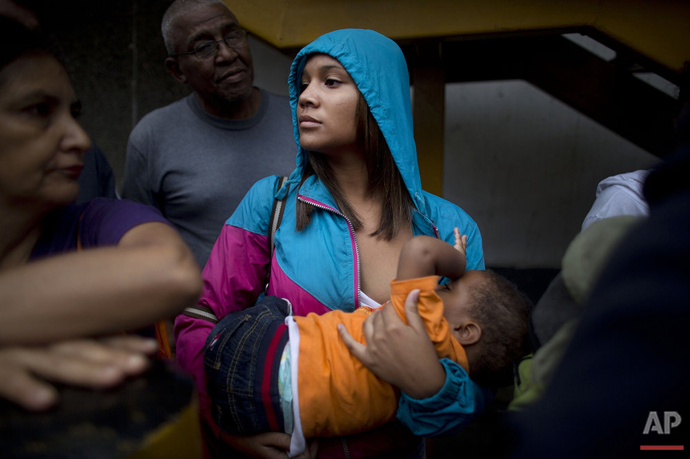 In this Tuesday, May 3, 2016 photo, Madeley Vasquez, 16, breast feeds her one-year-old son Joangel as she waits line outside a supermarket to buy in Caracas, Venezuela, Tuesday, May 3, 2016. Vasquez once had to run down the block to avoid getting caught up in a knife fight that broke out when a woman was accused of cutting the line. (AP Photo/Ariana Cubillos)