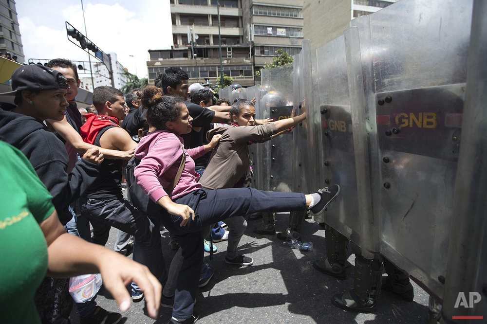 In this Thursday, June 2, 2016 photo, a woman kicks the shield of a National Guard soldier as other demonstrators push during a food protest a few blocks from Miraflores presidential palace in Caracas, Venezuela. Clashes broke out after people waiting for hours at a nearby grocery store learned a food supply truck was turned away. The shoppers got as close to the presidential palace as they could, and were joined by other demonstrators. (AP Photo/Ariana Cubillos)