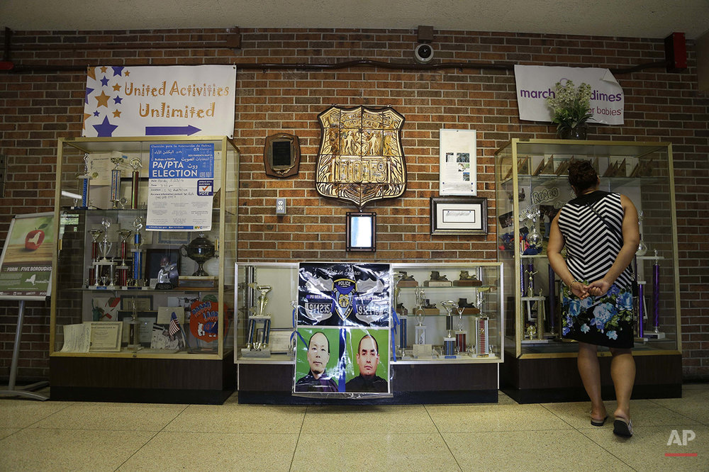 "This Wednesday, May 25, 2016 photo shows a memorial to New York City police officers Wenjian Liu and Rafael Ramos in the Police Officer Rocco Laurie Intermediate School 72 in Staten Island, New York. On Dec 20, 2014, they were ambushed and shot to death in their marked police vehicle without warning. ""A lot of kids in this school have parents who are police officers _ a lot,"" says Peter Macellari, principal of the school, where about a quarter of the students are Hispanic and 5 percent are black. He notes that Ramos was once the school's security officer. (AP Photo/Seth Wenig)"