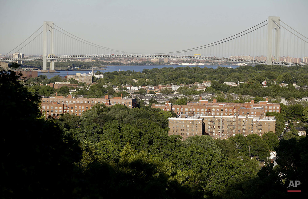 This Tuesday, June 14, 2016 photo shows the Verrazano–Narrows Bridge and the north side of the Staten Island borough of New York, foreground. Very few blacks live south of the Staten Island Expressway which continues from the bridge, and which some residents say amounts to a local Mason-Dixon line, reinforcing divisions of race and economics that shade the tensions around policing. (AP Photo/Seth Wenig)