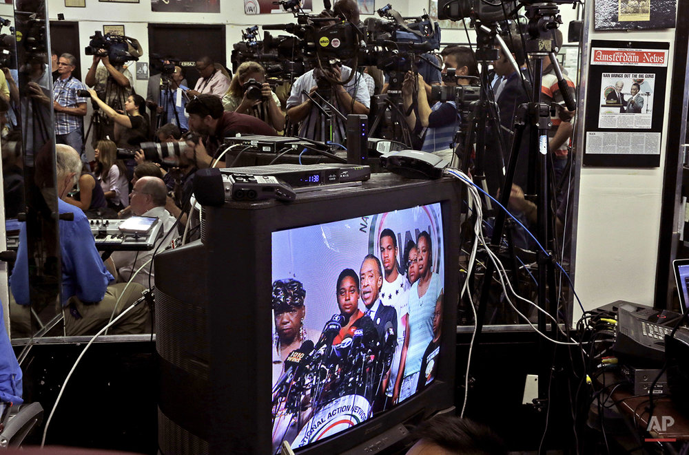 In this Tuesday, July 14, 2015 photo, The Rev. Al Sharpton, center, is seen on a television monitor, joined by Eric Garner's mother, Gwen Carr, left; daughter, Erica Garner, second from left; son, Eric Garner, third from left; daughter, Emerald Snipes, second from right, and wife, Esaw Snipes, during a news conference in New York. The family of Garner, a black man who died after being placed in a white police officer's chokehold, discussed the $5.9 million settlement it reached with the city days before the anniversary of his death. (AP Photo/Mary Altaffer)