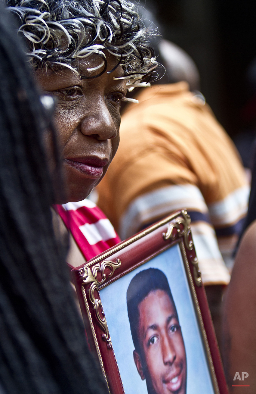 In this July 7, 2015, photo, Gwen Carr holds a picture of her son, Eric Garner, during a news conference in New York with relatives of other New Yorkers killed by police. The city reached a settlement with the family of Garner, almost a year after the 43-year-old died in police custody. That does not satisfy his mother. If her son's death means something, officials can clean up the block where regulars, black and white, say drinking and drugs have increased since his death. Confrontational cops are not the answer, she says. (AP Photo/Bebeto Matthews)