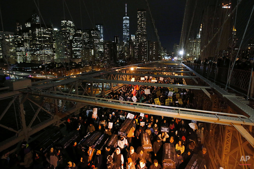 In this Thursday, Dec. 4, 2014 photo, demonstrators protesting a grand jury's decision not to indict the police officer involved in the death of Eric Garner, carry mock coffins bearing the names of victims of fatal police encounters, during a rally on the Brooklyn Bridge in New York. A day earlier, a grand jury cleared a white police officer in the videotaped chokehold death of the unarmed black man, who had been stopped on suspicion of selling loose, untaxed cigarettes. (AP Photo/Jason DeCrow)