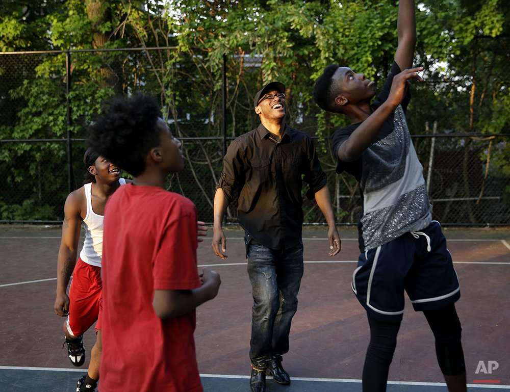 Leroy Downs plays basketball with local kids in the Staten Island borough of New York, Wednesday, May 25, 2016. Downs, 41, has lived on Staten Island since he was 5 and works as a drug treatment counselor. But he has thought about, just maybe, becoming a cop. It's not hard to imagine, given his almost paternal attention to the neighborhood. Except that Downs, has gone to court to fight the NYPD, and its widespread stop-and-frisks, mostly of black and Hispanic men. (AP Photo/Seth Wenig)