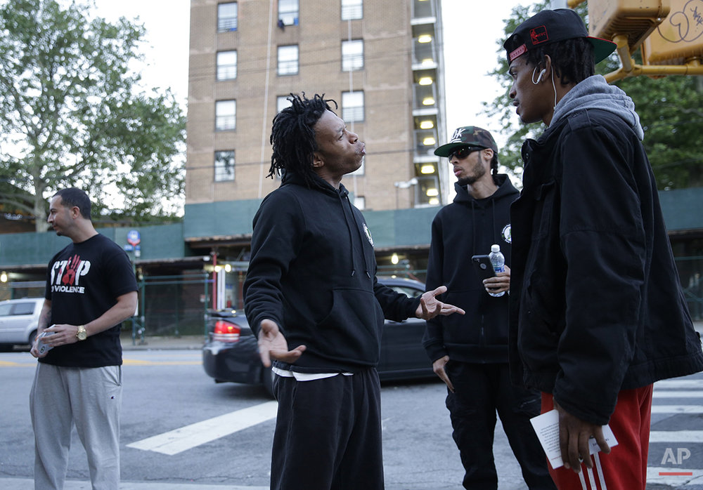 Members of the Cure Violence group talk with a man near the Stapleton Houses low-income housing complex in the Staten Island borough of New York, Wednesday, June 8, 2016. The group, five black men and one Latino, all acknowledge past crimes or prison time. Mike Perry, second right, used to deal drugs around another low-income housing complex, two miles away. Now, though, their team works to defuse arguments that can lead to shootings and match people with job training and counseling. (AP Photo/Seth Wenig)