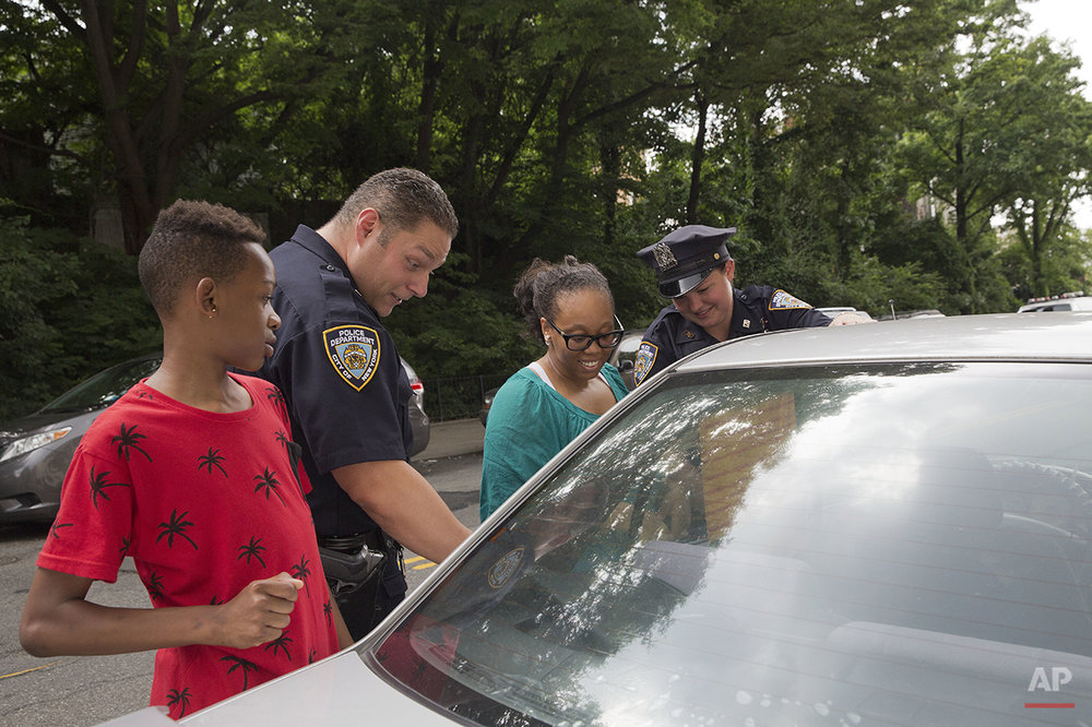 Police officers Mary Gillespie, right, and Jessi D'Ambrosio of the 120th precinct, help Monique Williams, center, after she accidentally locked her two children inside the car with the air conditioner running, at the Richmond Terrace Houses in the Staten Island borough of New York on Thursday, July 7, 2016. (AP Photo/Mary Altaffer)