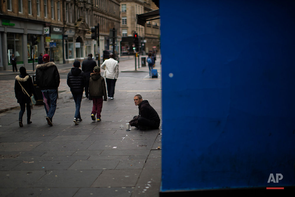 In this Sunday, July 3, 2016 photo, people walk by a beggar at a street in downtown Glasgow, Scotland. In one of the defining splits of last week's EU referendum, all 32 council areas in Scotland as well as Northern Ireland voted for Britain to stay in the bloc. Even towns shattered by the demise of shipyards, coal mines and steelworks made the calculus that quitting the EU wouldn't turn things around for them. (AP Photo/Emilio Morenatti)