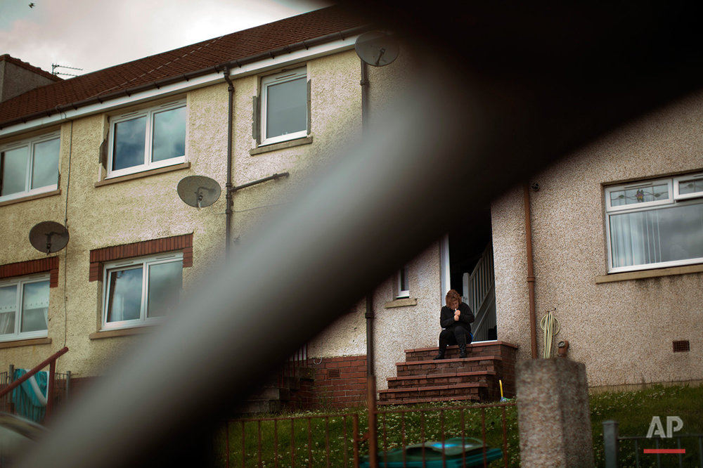 "In this Saturday, July 2, 2016 photo, a woman lights a cigarette as she sits on the steps of her house in Motherwell, southeast of Glasgow, Scotland. Motherwell, belongs to a council area where 62 percent of voters backed remaining in the EU. Places with the same recent history of decline in England and Wales typically voted ""leave"" by a similar margin. (AP Photo/Emilio Morenatti)"