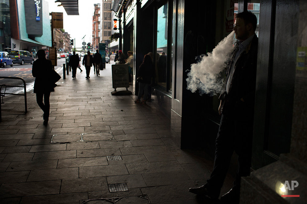 In this Friday, July 1, 2016 photo, a man smokes an electronic cigarette in downtown Glasgow, Scotland. In one of the defining splits of last week's EU referendum, all 32 council areas in Scotland as well as Northern Ireland voted for Britain to stay in the bloc. Even towns shattered by the demise of shipyards, coal mines and steelworks made the calculus that quitting the EU wouldn't turn things around for them. (AP Photo/Emilio Morenatti)