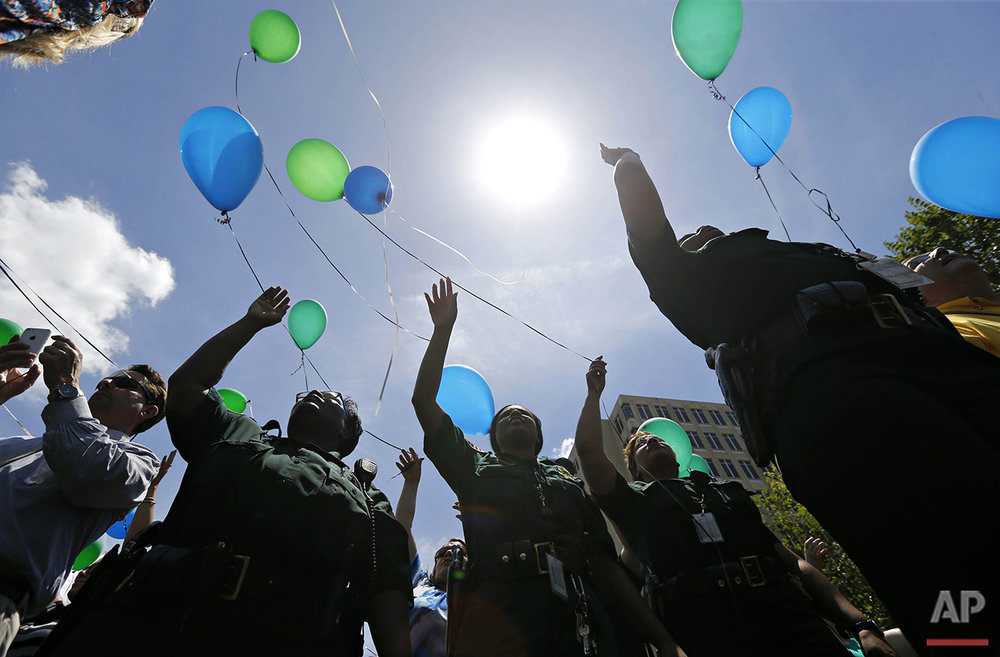 East Baton Rouge Sheriff's deputies release balloons at a noon vigil organized by municipal court workers in downtown Baton Rouge, La., Wednesday, July 20, 2106, in honor of recent slain and injured sheriff deputies and police. Several police officers and sheriff deputies were killed and wounded Sunday morning in a shooting near a gas station in Baton Rouge, less than two weeks after a black man was shot and killed by police here, sparking nightly protests across the city. (AP Photo/Gerald Herbert)
