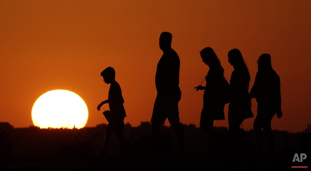 The sun sets behind visitors to Liberty Memorial in Kansas City, Mo., as the temperature hovers around 100 degrees on Thursday, July 21, 2016. The National Weather Service outlook for the next three months shows above normal temperatures across the country. (AP Photo/Charlie Riedel)