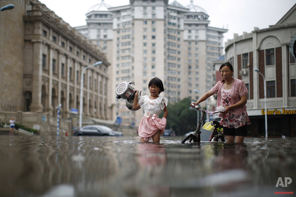 A child carries kettles through a flooded street with a woman in Tianjin, China on Wednesday, July 20, 2016 photo. At least 75 people in northern China have died or gone missing since Monday in some of the worst flooding in years, the government said Thursday. (Chinatopix via AP)