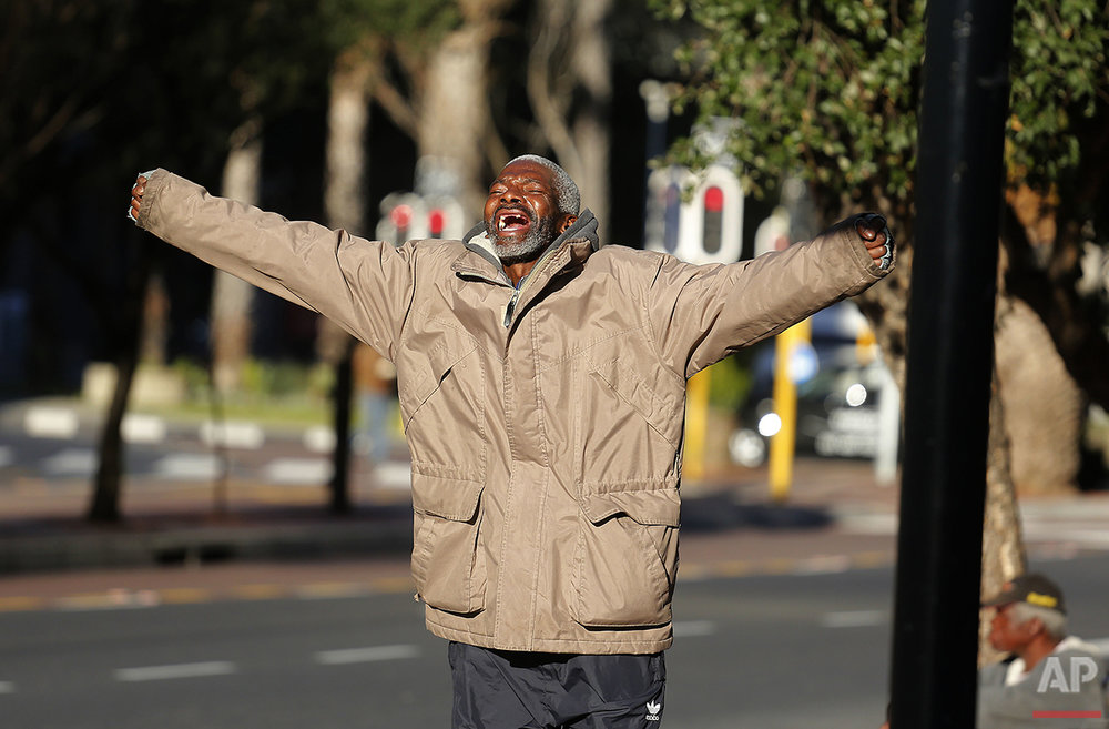 A destitute man shouts out on a city street were he and other homeless gather before nightfall in Cape Town, South Africa, Saturday, July 16, 2016. (AP Photo/Schalk van Zuydam)
