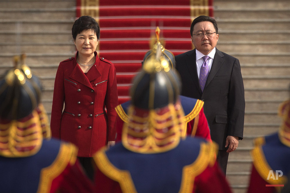 South Korea's President Park Geun-hye, left, and Mongolia's President Tsakhiagiin Elbegdorj, right, review an honor guard during a welcome ceremony in Ulaanbaatar, Mongolia, Sunday, July 17, 2016. (AP Photo/Mark Schiefelbein)