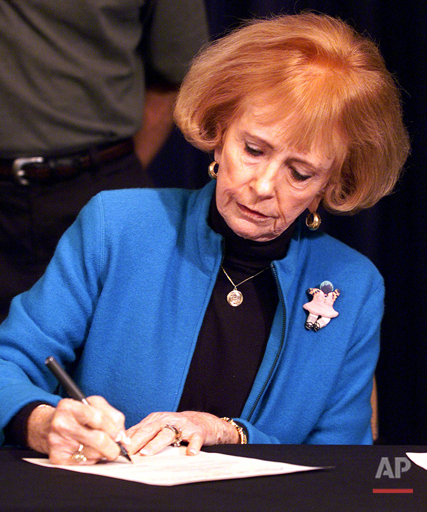 In this Nov. 9, 2000 photo, Arizona Gov. Jane Hull signs a call for a special session to change the State's costly alternative fuel vehicle program at the Capitol in Phoenix. Arizona voters broke the gender barrier in 1998 when they voted five women, including Hull, into statewide elected office and turned the state into the first in the nation to have an all-female elected line of succession. (AP Photo/Matt York)