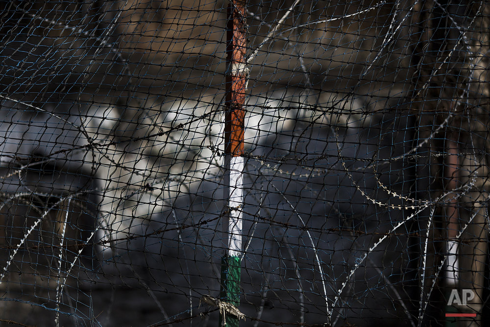 In this July 23, 2016 photo, barbed wire surrounds an Indian national flag in a paramilitary base in Srinagar, India-controlled Kashmir. Pakistan flags and local militias' flags are hoisted and waved on streets while Indian flags flutter on government buildings and forces camps. Kashmir, a predominantly Muslim region, is divided between India and Pakistan, but both claim it in its entirety. The rivals have fought two wars over control of Kashmir since independence from Britain in 1947. (AP Photo/Bernat Armangue)